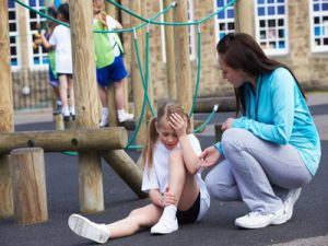 The picture shows a injuried girl on the playground with her worried mother