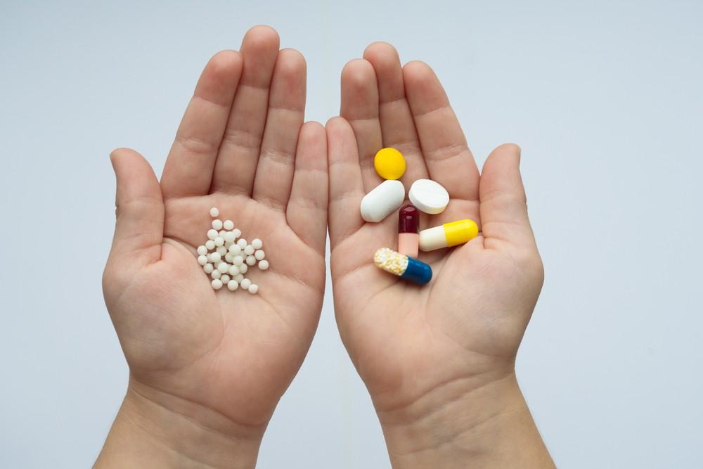 Zwei Handflächen. Links homöopathische Globuli, rechts pharmazeutische Medikamente.