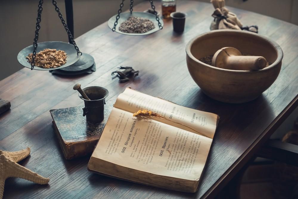 Tisch mit Buch und Zubehör für homöopathische Zubereitungen